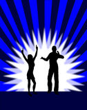 Blue Disco Dancers. A group of dancers in silhouette on a stage in front of a blue and black background with a white light in the centre.  The additional format Stock Photography