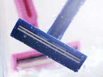 Blue disposable razor in water with bubbles stock photo