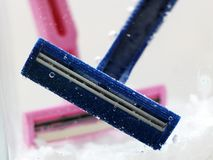 Blue disposable razor in water with bubbles stock photography