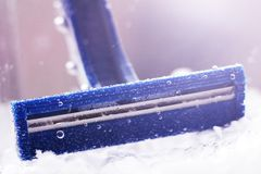 Blue disposable razor in water with bubbles royalty free stock image