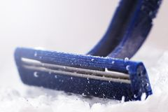 Blue disposable razor in water with bubbles stock photos