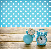 Blue doll roly-poly, old alarm clock. Blue doll roly-poly and old alarm clock on a wooden table, retro style Stock Image