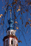 Blue Dome of an ancient Orthodox church. Dome of an ancient orthodox cathedral against the clear sky in an environment of birch branches in the fall Royalty Free Stock Photo