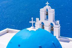 Blue dome and bell tower of famous Agios Theodori Church in Firostefani. Facing Aegean Sea Santorini Greece royalty free stock photography