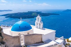 Blue dome and bell tower of famous Agios Theodori Church in Firostefani. Famous Agios Theodori Church with blue dome and bell tower in Firostefani facing Aegean royalty free stock image