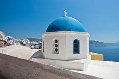 Blue dome of a white church with Caldera cliff in a background, Oia village, Santorini island Royalty Free Stock Images