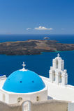 Blue-domed chapel with ochre bell tower in Oia Stock Photo