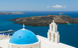Blue-domed chapel with ochre bell tower in Oia Royalty Free Stock Photos