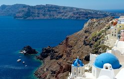 Blue domes of Santorini. The blue dome of the Christian church and the bell tower looking beautiful against the blue sea and the caldera of Santorini Stock Photos