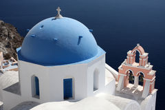 Blue domes and their bell tower in Oia Stock Images