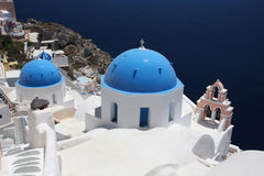 Blue domes and their bell tower in Oia. santorini. Royalty Free Stock Photography