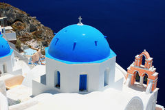 Blue domes and their bell tower in Oia Stock Image