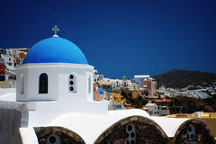 Blue domes and their bell tower in Santorini Stock Image