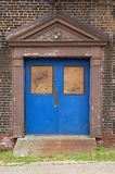 Blue door. Entrance to an old building painted bright blue.  The rest of the building is in dis-repair Stock Photography