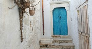 Blue door against white wall. Blue door outside whitewash walls in Cyclades, Greece Stock Image