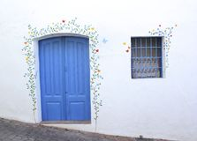 A blue door and barred window with a flower mural on the white washed wall Stock Photo