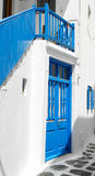 Blue door with Blue Stairs. White washed walls frame a blue door and staircase Royalty Free Stock Image