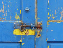 Blue door, bolted. Peeling blue paint on the door of a fisherman's hut in Whitstable Stock Photo