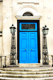 Blue door and the classic facade with metal lamps Stock Images
