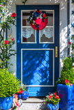 Blue door decorated with red hat and blue pottery Royalty Free Stock Images