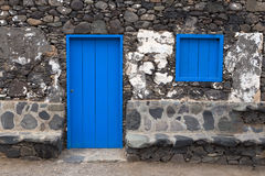 Blue door and hatch in a house. Blue door and hatch in a simple house made of black boulders Royalty Free Stock Photography