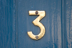 Blue door number 3. A brass number three on a blue door Stock Photo