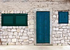 Blue door and shutters in old stone house Stock Photography