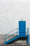 Blue door and stairs. Blue, metal warehouse entry door with stairs royalty free stock photos