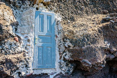 Blue door standing in the middle of the rock, leading nowhere Royalty Free Stock Image