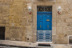 Blue door of a stone house, island Malta. Bright blue door - entrance to an old stone house. Decorative lanterns with the maltese cross base. Seglea, island Royalty Free Stock Photos
