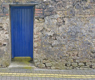 Blue Door in a Stone Wall. A blue, wooden door, set into a stone wall, in front of double yellow lines Royalty Free Stock Images