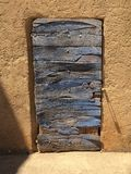 Blue Door. A weathered blue wooden door stands out on a stone background in Provence, France Royalty Free Stock Photo