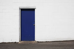 Blue door on white building. Deep blue door on white building Royalty Free Stock Photos
