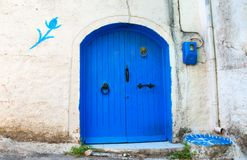 Blue Door in a White Wall. With a flower sign Stock Image