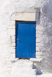 Blue door on white wall Stock Photography