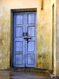 Blue Door in Yellow Walls. Blue door on yellow Walls of an old ruined house in India locked for years Stock Photo
