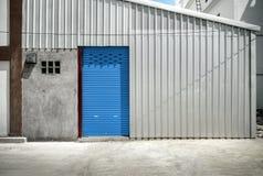 Blue door and zinc wall of warehouse Stock Photos