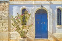 The blue doors in old house, Naxxar, Malta. The blue door with tight windows of the residential house in Naxxar town, Malta royalty free stock image