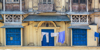 Blue doors and shutters of typical houses with roof life in old Delhi, India Royalty Free Stock Photos