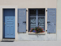 Blue doorway and shuttered window Stock Photos