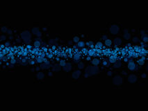 Blue dots on black. An illustrated view of a horizontal streak of various sized blue dots in the middle of a black background Royalty Free Stock Image