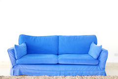 Blue double sofa on a blank wall. A double blue couch sofa on a blank wall in a living room Royalty Free Stock Photo