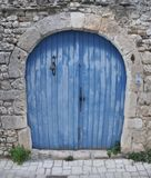 Blue double wing door with bell. Blue wooden double wing door with bell in an old stone wall in southern France royalty free stock photos