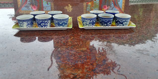 Blue dragon Chinese tea cup and reflection of dragon on red marble altar Royalty Free Stock Images