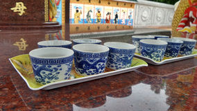 Blue dragon Chinese tea cup and reflection of dragon on red marble altar Stock Image
