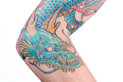 Blue Dragon Tattoo on Arm. A detailed shot of a blue/green dragon tattoo in Japanese style on the forearm, elbow and bicep of a white male isolated on a white royalty free stock photo