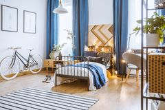Blue drapes in cozy bedroom. Blue drapes and bicycle in cozy bedroom interior with plants on cupboard next to a bed with lights Royalty Free Stock Photos