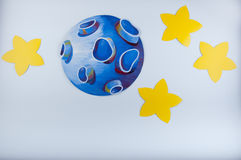 Blue drawn planet and yellow stars around lay on white background Stock Photo