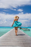 Blue dreams. Beautiful woman walking down pier in sarong Stock Images