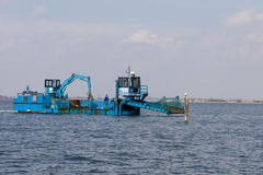 Blue dredger on water Royalty Free Stock Photography